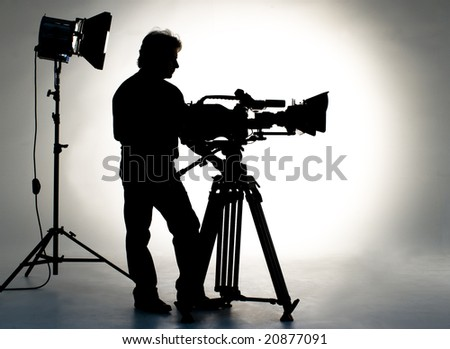 Searchlight and silhouette of the camera and cameraman. - stock photo