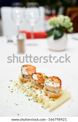 Seared scallops with white asparagus and cream sauce on restaurant table - stock photo