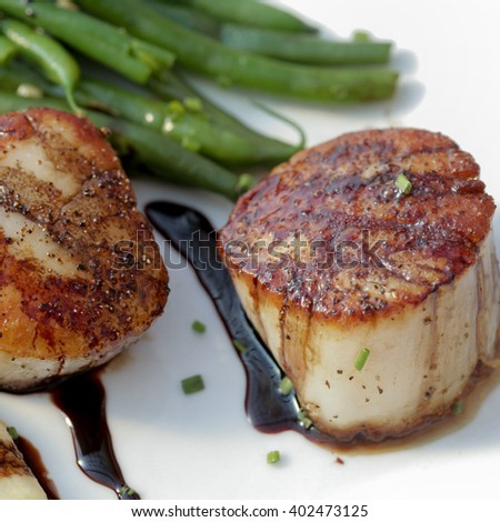 Seared sea scallops with polenta, green beans and red wine syrup - stock photo