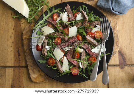 Seared steak, rocket and tomato salad topped with grated Parmesan - stock photo