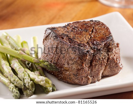 seared tenderloin steak with asparagus. - stock photo