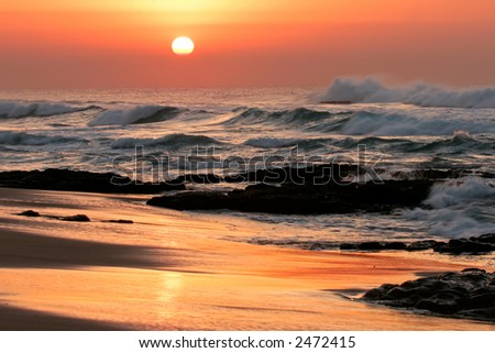 Seascape at sunrise with golden reflections and rocks in foreground - stock photo
