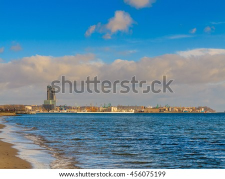 Seascape. Baltic sea bay Poland. Waves on the shore of the sandy beach. City Gdynia and port in the background. - stock photo