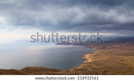 Seascape color landscape photo. Mountain sea shore with yellow hills and capes cliffs. Calm sea and blue sky with white clouds. It is photographed in the fall in cloudy day. - stock photo