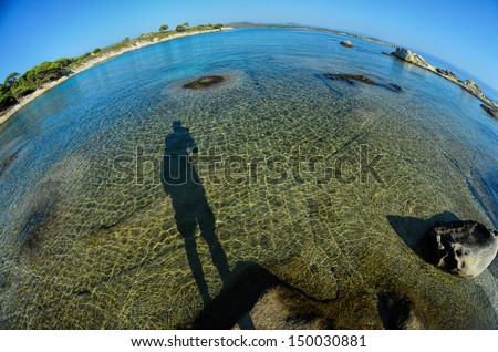 Seascape fish eye view with a huge stones and shadow of photographer in morning sunlight, Carydi beach, Chalkidiki, Sithonia, Greece - stock photo
