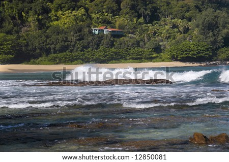 Seascape includes crashing waves, reef, beach and beach home on cliff above bay.  Lush tropical foliage surrounds home. - stock photo
