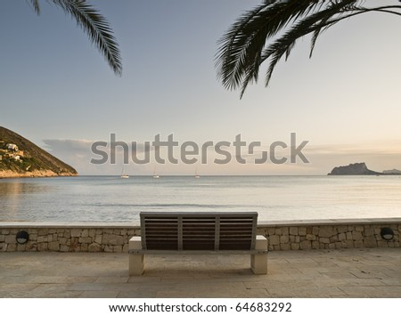 Seascape of a beach on the Costa Blanca of Spain, with the famous Rock of Ifach on the background and a bench in the foreground. The image is framed by two palm branches. - stock photo