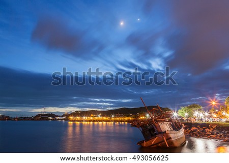 Seascape of dust sunset with dead fishing boat at Chonburi province, Thailand