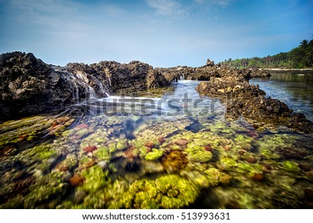 Seascape scenery of beautiful green coral formation during mid day at Sawarna beach, Banten, Indonesia. Soft focus during long exposure shot.