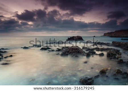 Seascape. Seashore with misty water at sunset - stock photo