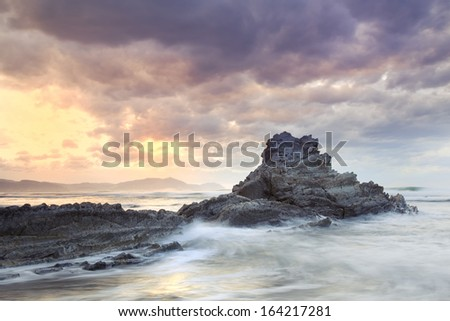 Seascape showing waves breaking against a rock on the coast with a cloudy stormy sky and the sun appearing in the background - stock photo