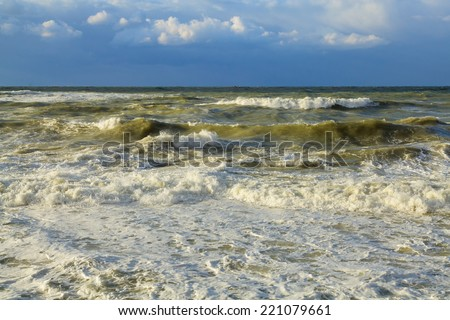 Seascape. Storm in ocean with big windy waves. Nature composition on a background blue sky with white clouds. - stock photo