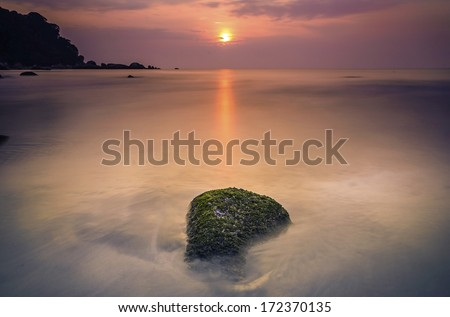 Seascape view in sunrise at beach. Slow shutter mode. - stock photo