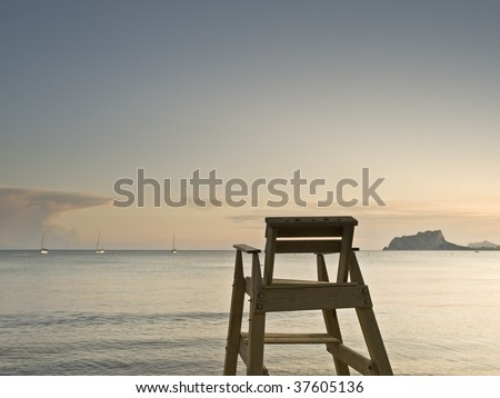 Seascape with a lifeguard chair on the foreground facing to the sea, with some sailboats and a mountain on the background - stock photo