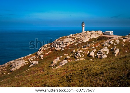 Seascape with a lighthouse over the rocks and a blue sky - stock photo