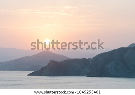 Seascape with a view of the mountains. Summer evening by the sea. Sunset in gentle pastel colors. Natural background for placing text