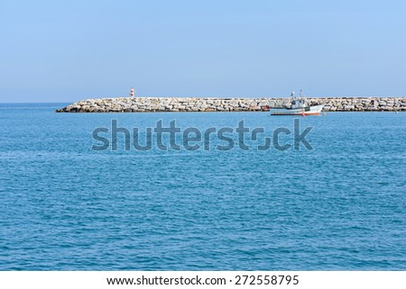 Seascape with blue sea, sky and seawall - stock photo
