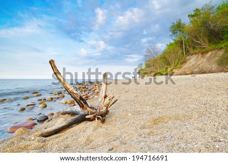 Seascape with coastal stones in the ocean and trunk on beach. The Baltic coast, mediterranean sea, Poland. - stock photo