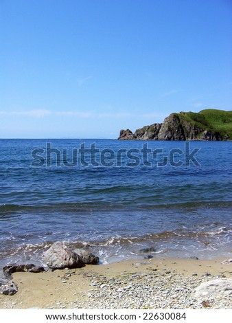 Seascape with high blue sky, clear sea water, cliff and coastline