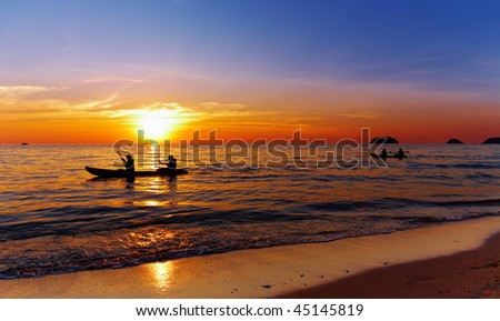 Seascape with kayakers at sunset, Chang island, Thailand - stock photo