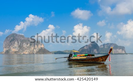 Seascape with limestone mountain and wooden long-tail boat at Pak Meng Beach in Trang province, Thailand - stock photo