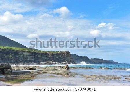 Seascape with ocean and rocks and clouds in the sky on a sunny day. Beautiful tranquil landscape in New South Wales, Australia.  - stock photo