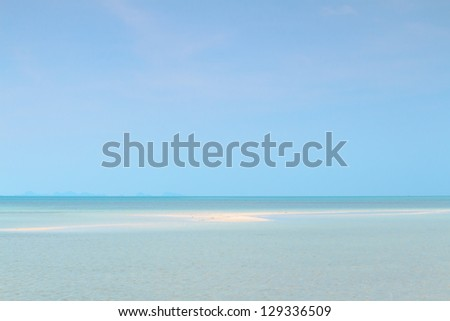 Seascape with puffy white clouds,sand and blue sky - stock photo