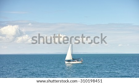 Seascape with sailboat the background of the blue sky and white clouds. - stock photo