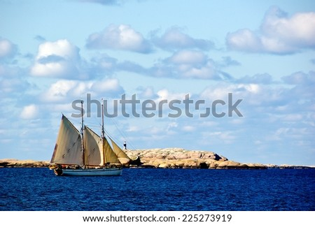 Seascape with sailing ship, red granite boulders and blue sky at the swedish west coast.