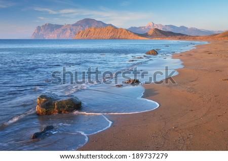 Seascape with sandy beach. Sunny morning on the sea. Coast with rocks and cape. The peninsula of Crimea - stock photo