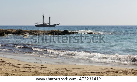 Seascape with touristic sail ship, sand beach and rocks in Paphos, Cyprus.