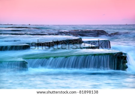 Seascape with water flowing over interesting rocks. Slow shutter speed. - stock photo