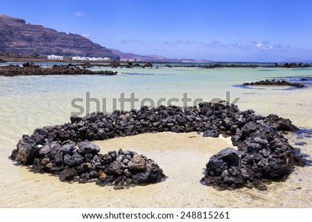 Seascape with wind protection volcanic rocks and small village in Lanzarote, Canary islands, Spain - stock photo