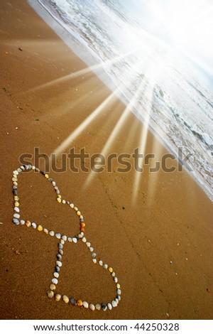 Seashell hearts and sun rays - stock photo
