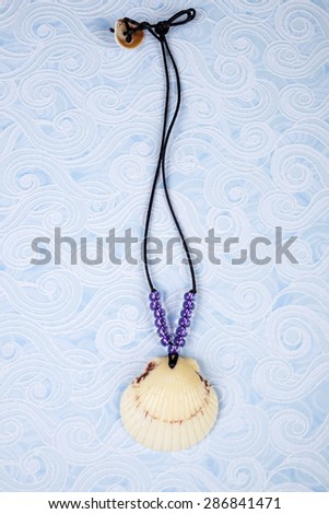 Seashell necklace with a black satin cord, scallop pendant decorated with purple beads and a clasp made with a small seashell. - stock photo