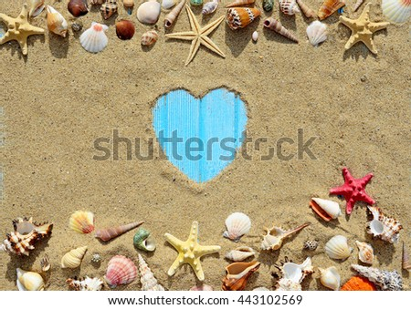 Seashells and starfish on a old wooden background. Silhouette of the heart made of sand - stock photo