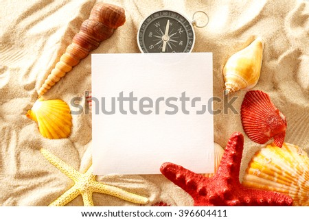 Seashells, compass and blank paper on sand - stock photo