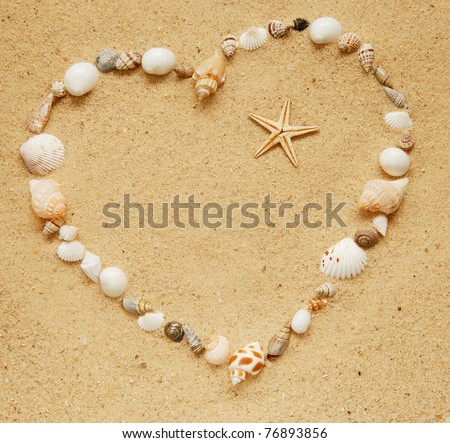 seashells in the shape of a heart with a small starfish inside - stock photo