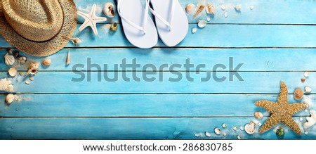 seashells on  blue wooden plank with straw hat and flip-flop -  summer holiday background  - stock photo
