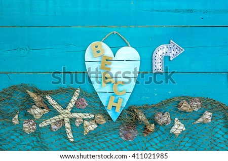 Seashells, starfish and fish net border on antique rustic teal blue wood background with metal direction arrow; broken heart beach sign - stock photo