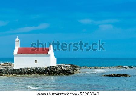Seashore of Hersonissos with a church, touristic place in Crete, Greece. - stock photo