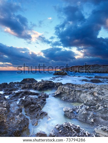 Seashore with reflections in water during sundown. Composition of the nature