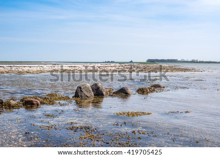 Seashore with rocks in the water in daylight - stock photo