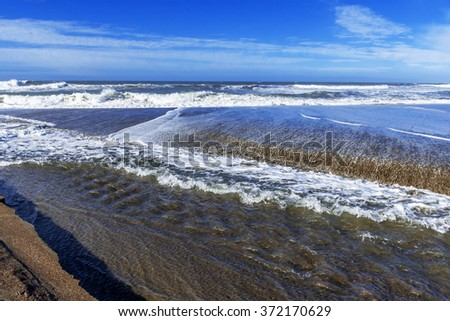 Seaside creek meets the ocean, blue sea & sky, white clouds, heavy surf / waves, at high tide, along a rocky coastline, traveling the Big Sur Highway (Highway 1) on the California Central Coast. - stock photo