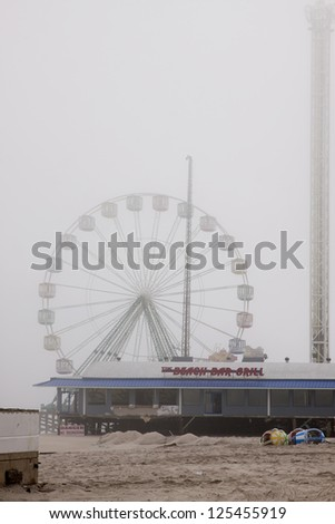 SEASIDE HEIGHTS, NJ - JAN 13:The FunTown Pier Giant Ferris Wheel in the fog on January 13, 2013 in Seaside Heights, New Jersey. Clean up continues 75 days after Hurricane Sandy struck in October 2012. - stock photo