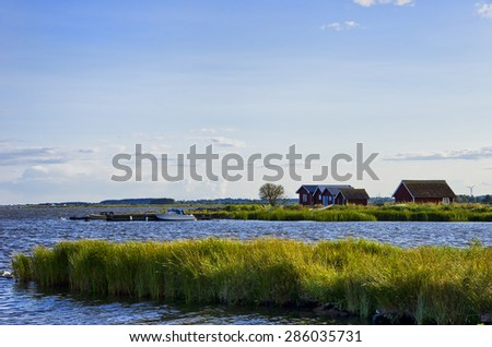 Seaside Idyll - Seaside idyll in the evening light with huts and boats on the island of O?land, Sweden.