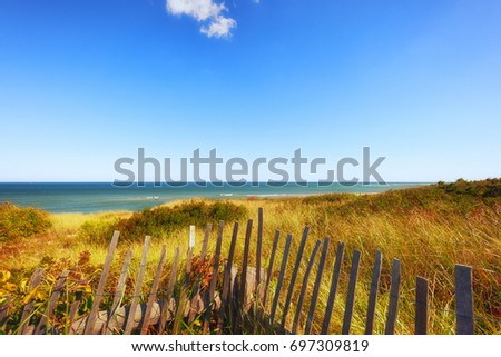 Seaside view of Highland light beach on Cape Cod in Massachusetts.  Fencing boarders the sea grass growing on low sand dunes that lead the eye to the horizon over the sea.