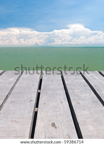 Seaside wooden bridge with beautiful cloudy and emerald color backwater sea - stock photo