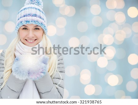 season, christmas, holidays and people concept - smiling young woman in winter clothes over lights background - stock photo