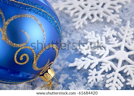 Seasonal arrangement with blue-gold bauble and beautiful snowflakes - stock photo